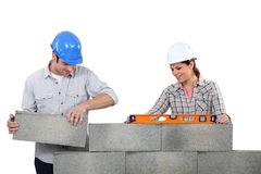 Man and woman building wall Royalty Free Stock Image