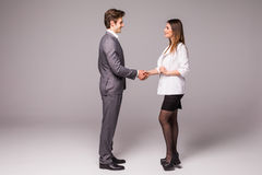 Man and woman business handshake isolated on gray background. Businessman and business woman handshake. Royalty Free Stock Photography