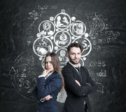 Man and woman and business icons on blackboard. Portrait of two business partners sanding near a concrete wall with business icons forming a circle on a Royalty Free Stock Photos