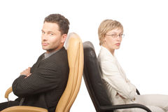 Man and woman - business partners. Business man and woman are sitting on the chairs - isolated Stock Images
