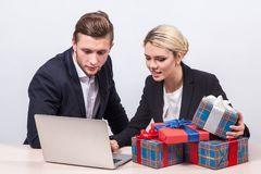 Man and woman in business suits sitting at a desk in front of la. Man and women in business suits sitting at a desk in front of laptop surrounded by gifts and Royalty Free Stock Images