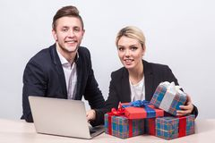 Man and woman in business suits sitting at a desk in front of la. Man and women in business suits sitting at a desk in front of laptop surrounded by gifts and Stock Images