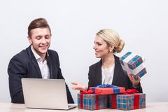 Man and woman in business suits sitting at a desk in front of la. Man and women in business suits sitting at a desk in front of laptop surrounded by gifts and Royalty Free Stock Photo