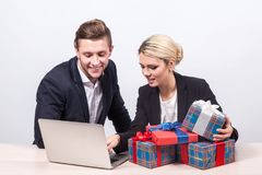 Man and woman in business suits sitting at a desk in front of la. Man and women in business suits sitting at a desk in front of laptop surrounded by gifts and Royalty Free Stock Image