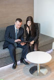 Man and woman in business suits sitting on the sofa Stock Photos