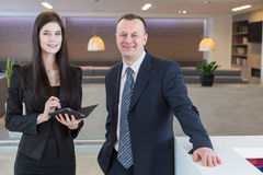 Man and woman in business suits standing at the reception stock photos