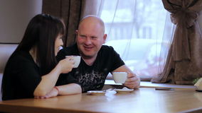 Man and woman in cafe. Young man and woman using tablet in cafe stock footage