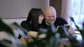 Man and woman in cafe. Young man and woman using tablet in cafe stock video