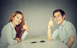Man woman with call me gesture sitting at table. Man and women with call me hand gesture sitting at table royalty free stock photo