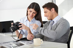 Man and woman with camera in office. Man and women sitting with camera in office and looking at photos Royalty Free Stock Photography