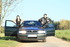 Man and woman by a car. Young men and women in black standing aside a new gren car Royalty Free Stock Photos