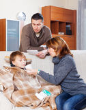 Man and woman caring for sick teenager. Man and women caring for sick teenager boy at home royalty free stock photography