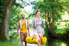 Man and woman carrying canoe to forest river. Man and women carrying canoe to forest river in summer stock photos