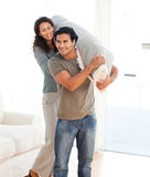 Man and woman carrying a carpet together Stock Photos