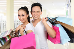 Man and woman carrying shopping bag. Portrait of happy men and women carrying shopping bag at the mall Royalty Free Stock Image