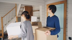 Man and woman with carton boxes are opening door, entering their new house, looking around and kissing then going. Upstairs carrying things. Relocation and stock video