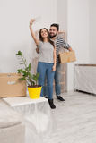 Man and woman in casual clothes standing in new home after relocation, forwarding to new life. Royalty Free Stock Photography