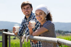 Man and woman chatting and enjoying milk outdoors. Happy men and women chatting and enjoying milk outdoors royalty free stock photography