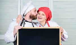 Man and woman chef cooking food together. Couple with blackboard for advertisement. Lovely family at kitchen. Family. Man and women chef cooking food together stock photo