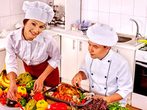 Man and woman in chef hat cooking chicken Stock Image
