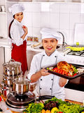 Man and woman in chef hat cooking chicken Royalty Free Stock Photos