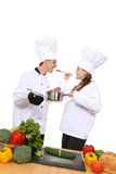 Man and Woman Chefs. Attractive man and woman chefs cooking and tasting food Royalty Free Stock Image