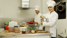 Man and woman chefs cooking food stock footage
