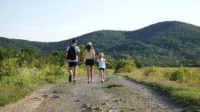 Man, woman and child go by a straight mountain road. Back view of family walking on the trail. stock footage