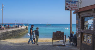 Man,woman and child walking past the town beach in Corralejo Royalty Free Stock Images