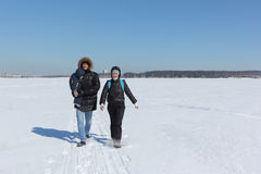 Man, woman and the child walking on the snow river in the winter Stock Photo