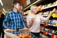 Man and woman are choosing cheese in department store Stock Photos