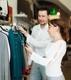 Man and woman choosing clothes at shop Stock Photography