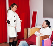 Man and woman choosing coat in fitting-room Royalty Free Stock Photo