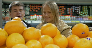 Man and woman choosing oranges. Young man and woman going shopping for fruit. Smiling people taking fresh oranges from showcase stock video