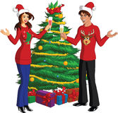 Man and Woman at Christmas party with drinks. Happy young couple with Christmas sweaters in front of decorated tree with gifts holding drinks and having party royalty free stock photo
