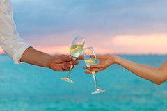 Man and woman clanging wine glasses with champagne at sunset Royalty Free Stock Images