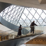 Man and woman climb spiral staircase at The Louvre Paris royalty free stock photo