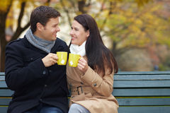 Man and woman clink glasses. Man and women clink glasses with hot tea in autumn Stock Image
