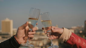 Man and woman clink glasses with champagne. Close-up. Beautiful urban view on blurred background. Female`s and male`s hands holds a glasses with champagne. The stock video footage