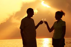 Man and woman clink glasses. Summer evening. Royalty Free Stock Images