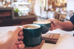 A man and a woman clinking green coffee mugs in cafe. Close up image of a man and a woman clinking green coffee mugs in cafe stock images