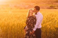 Man and woman with closed eyes embracing and kissing in wheat field on the dusk. Man and women with closed eyes embracing and kissing in wheat field on the dusk royalty free stock image