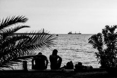 Man and woman on coastline in the port on end at of the end of the day - grayscale, grained Royalty Free Stock Photos