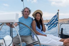 Man and woman in cockpit of sailboat stock photo