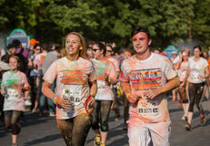 Man and woman in color run. Boy and girl couple at running competition covered with yellow and orange powder. Brightly colored face, happy and smiling, crowd of Stock Photos