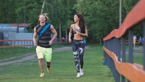 Man and woman commit a jog. They are young and attractive, communicate with each other positively. stock video footage
