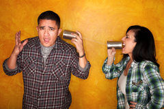 Man and woman communicate through tin cans Royalty Free Stock Photos