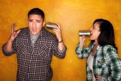 Man and woman communicate through tin cans. Attractive Hispanic man and woman communicate through tin cans Royalty Free Stock Photos