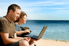 Man and woman with computer at beach Stock Photography