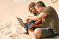 Man and woman with computer at beach Royalty Free Stock Image